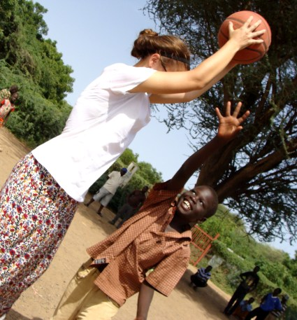 Maria plays with one of her young students during a basketball tournament.
