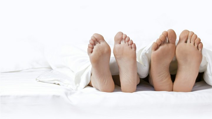 two pairs of feet in bed underneath white sheets