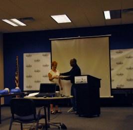 Pamela Mathews receiving her attendance card