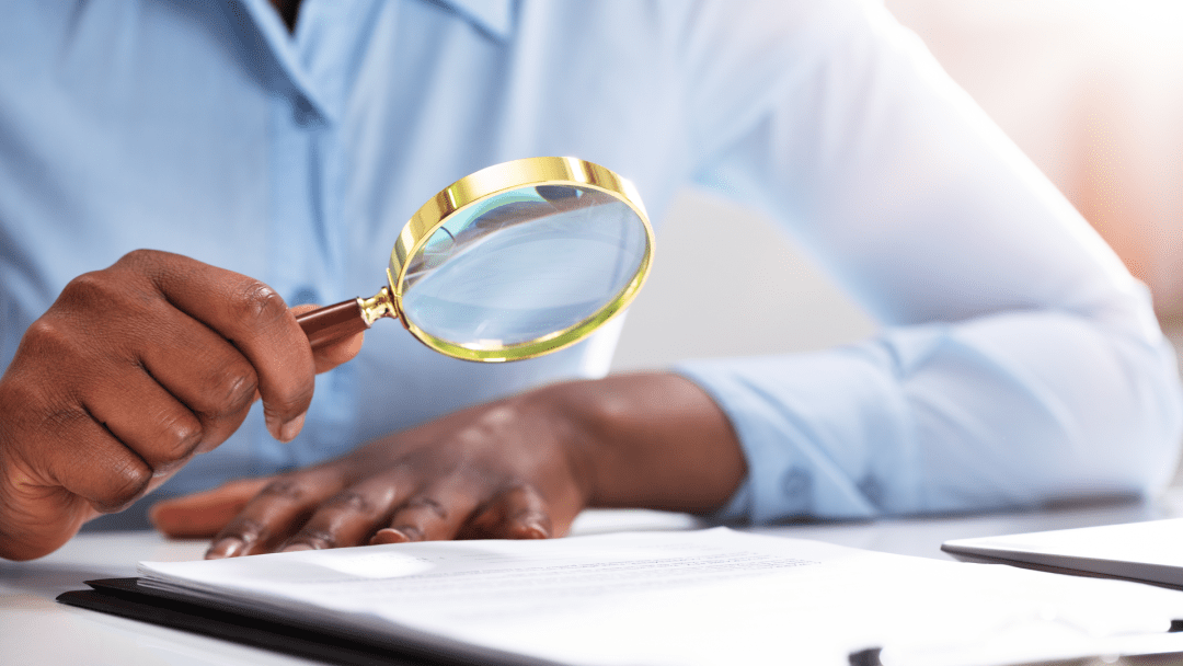 Woman looking at a factsheet through a magnifying glass