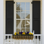 Shutters surround a window on a home's porch