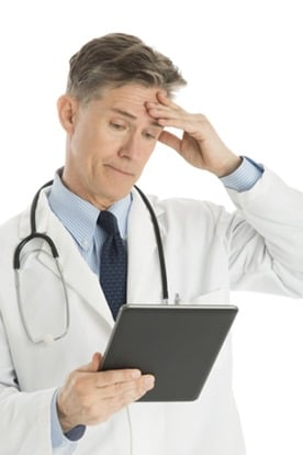 Confused Male Doctor Looking At Digital Tablet