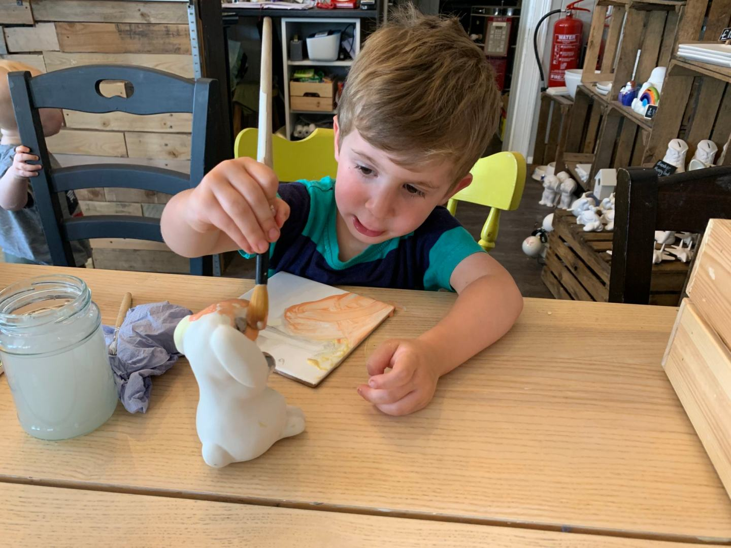 Child paints a pottery rabbit