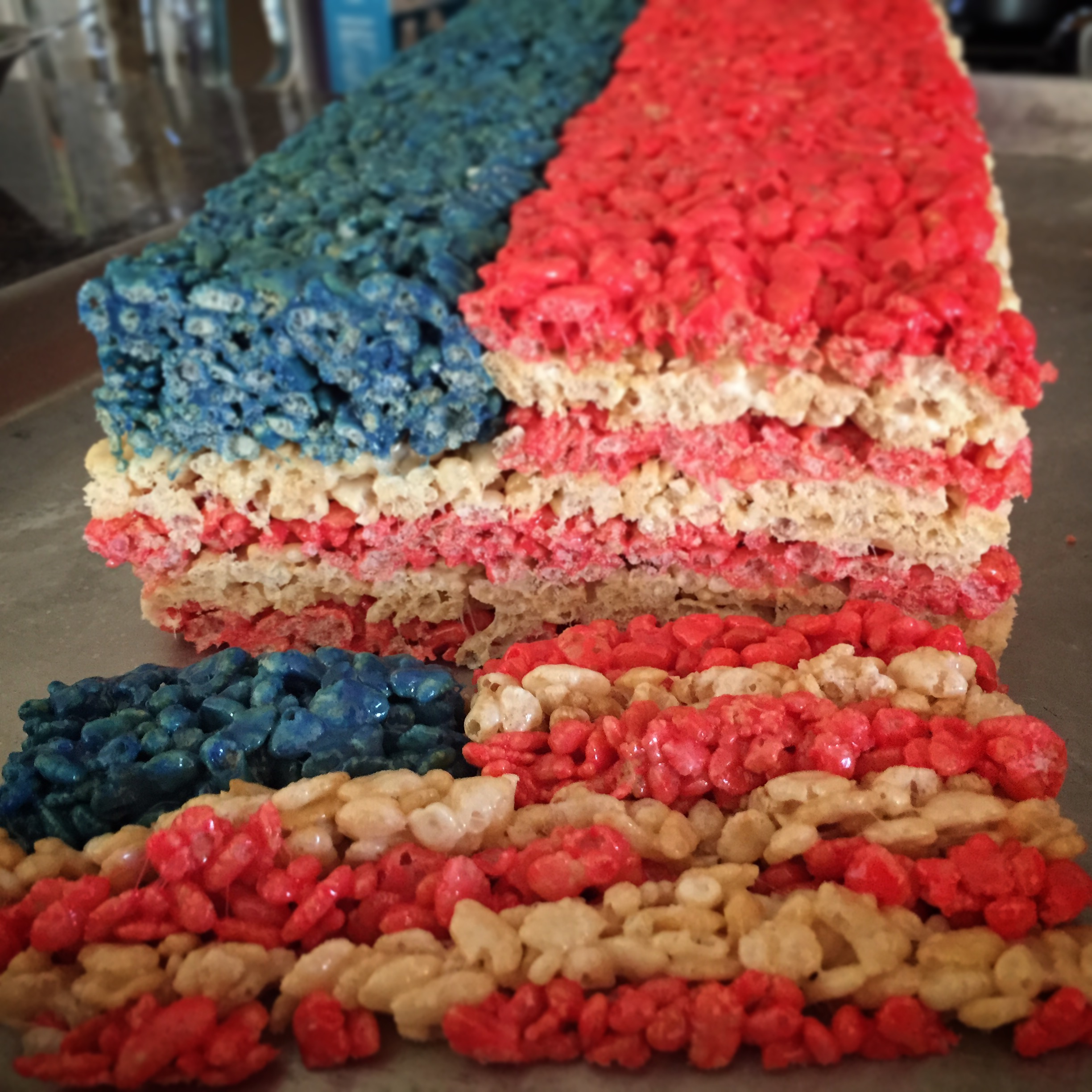 A long rectangle of rice krispie treats with one slice removed. The cross-section reveals an American Flag design.