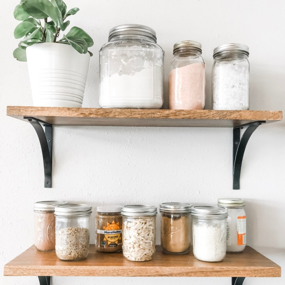 Food decanted in glass mason jars on open shelves in minimalist kitchen