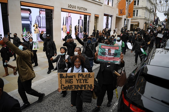 Protestors raise their fists during a protest action against police brutality in Nigeria, as they kneel in New Cavendish Street in central London on October 24, 2020.