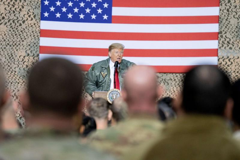 FILE PHOTO: US President Donald Trump, in 2018, speaks to military leadership members during a visit to al-Asad Air Base, Al Anbar, Iraq