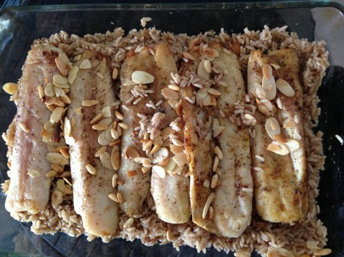 Lay the onion rice and top with fish fillets and nuts