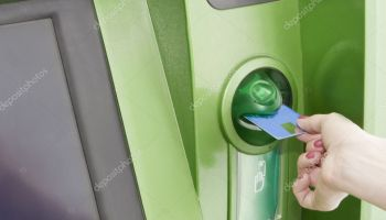 Female inserts a plastic card in the ATM. Banking Equipment.