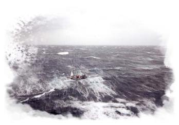 Aerial image of a sailboat hove to during a storm