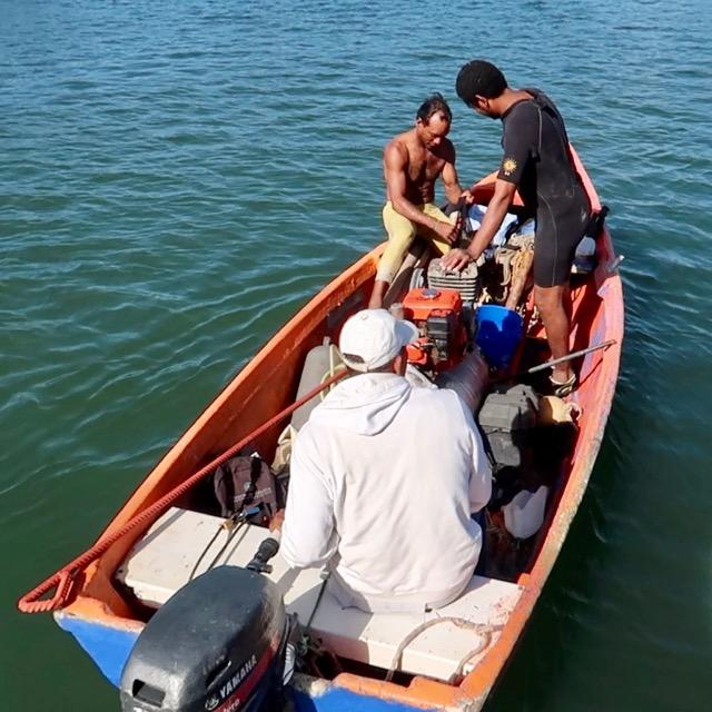 Photo of 3 men in a boat