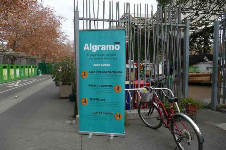 The Algramo refilling tricycle is parked next to the municipal recycling station