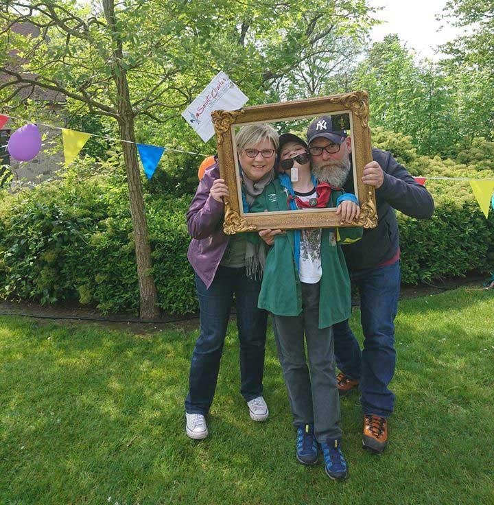 Famille avec un enfant en photo dans un cadre. L'enfant porte l'uniforme des Louveteaux.