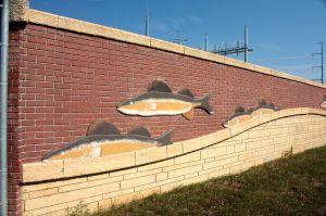 A decorative wall with a river motif hides High Bridge power plant equipment.
