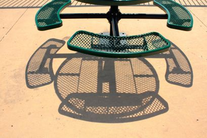The sun passing through a picnic table casts an interesting shadow pattern on the ground.
