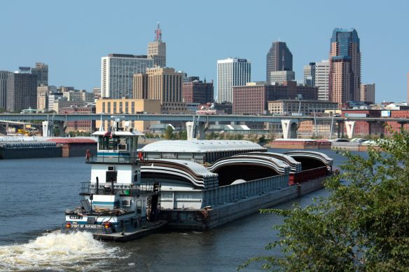 "The ""Mary J"" moves two barges upriver. Downtown Saint Paul is in the background."