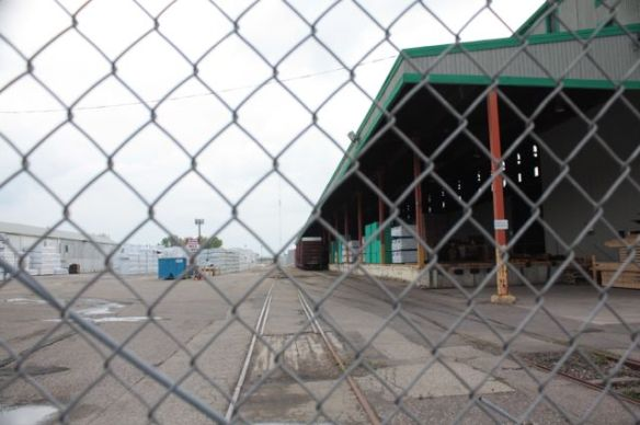 Peering through the fence of the Weyerhaeuser distribution facility, one can see what appear to be packages of lumber ready for delivery.