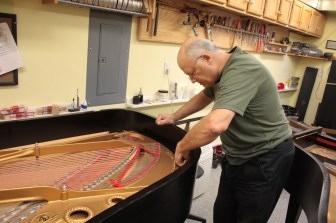 Mark checks the strings of one of the Steinway pianos in his workshop.