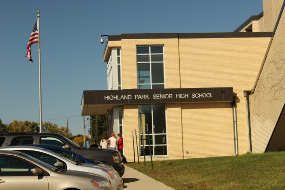 A few students linger outside the main entrance to Highland Park High School after the end of the school day