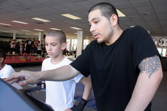 A trainer explains the treadmill to a young customer.