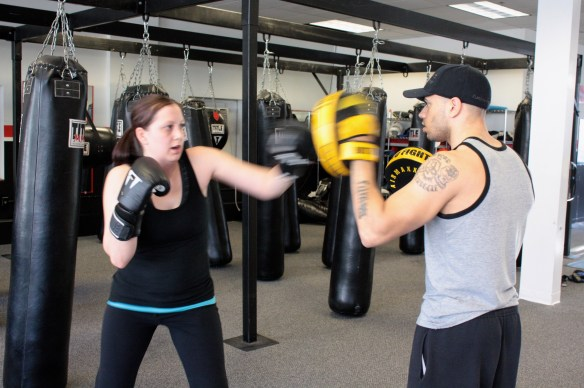 Dalton helps a client with her punching technique.