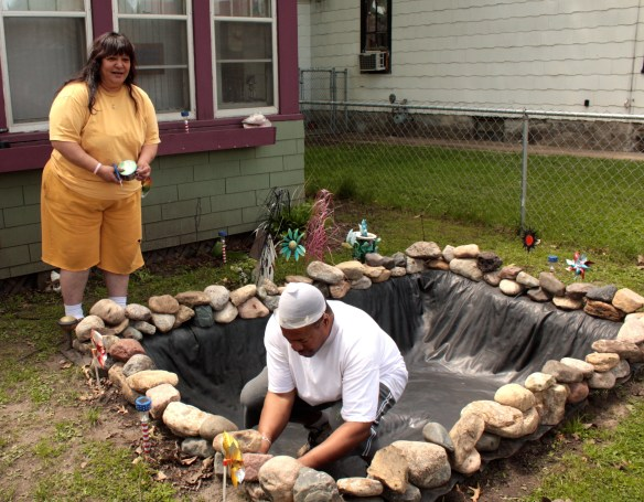 Allen and his wife Erma patch holes in the pond liner with duck tape.