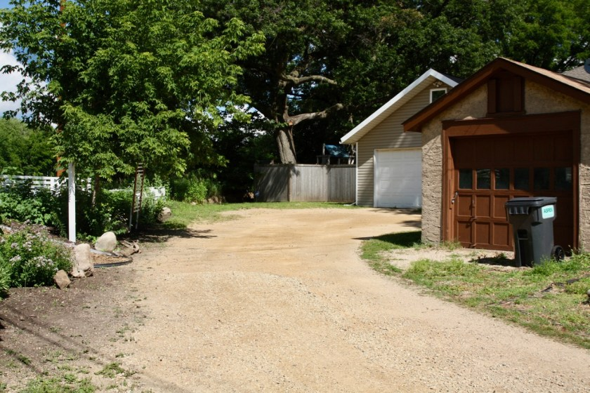 Two garages on the east side of the alley, and some landscaping on the top of the hill overlooking Ayd Mill Road.