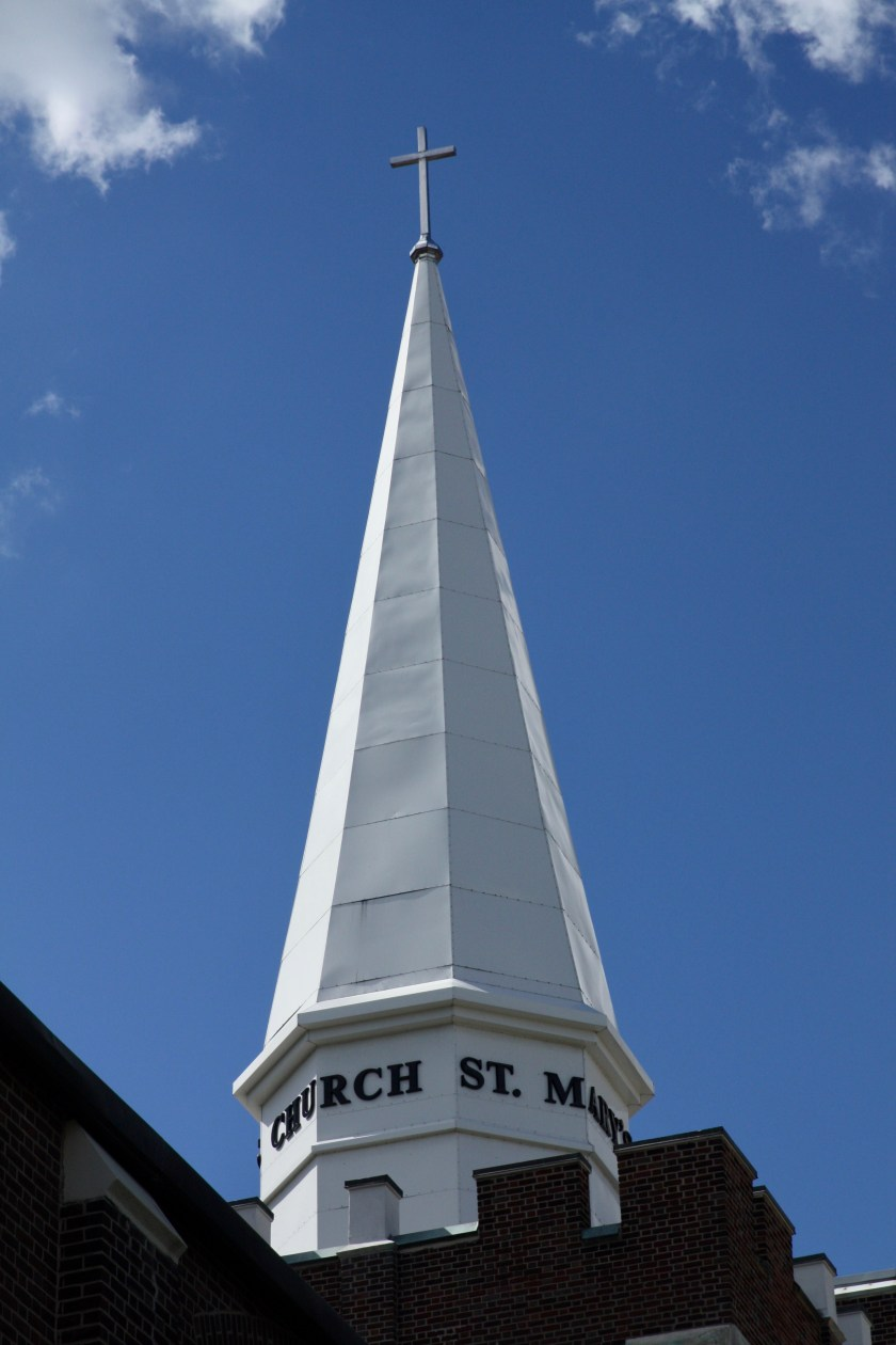 The brilliant white steeple of St. Mary's Catholic Church stood in impressive contrast to the azure sky.