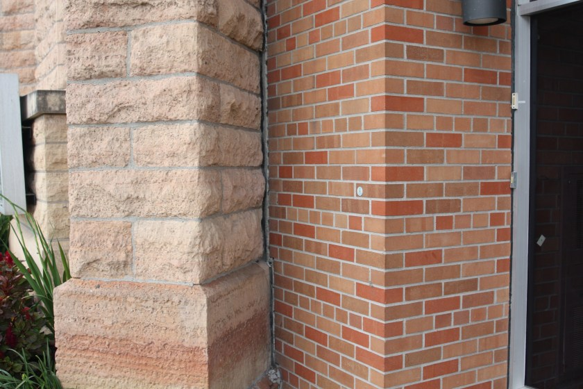 The stone work of 1875 building and the brick of the 1967 addition meet on the Wacouta Street side.