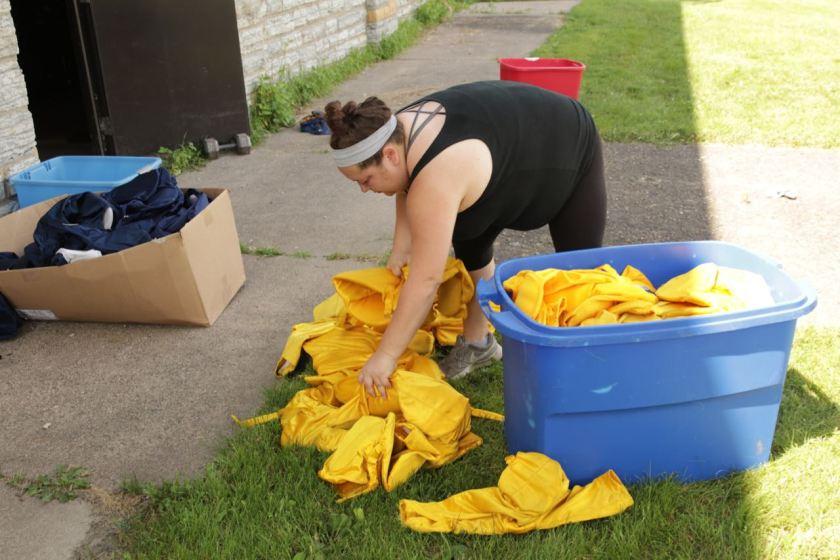 Marissa sorts football pants by size.