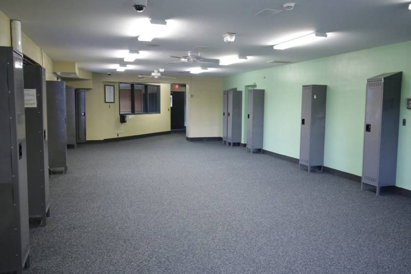 The second floor dorm with nothing but empty lockers remaining. An empty office is behind the three windows.