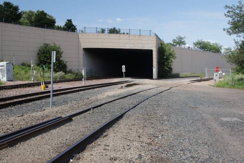 Several railroad tracks pass by the west end of James Avenue. Trains run through the tunnel while vehicles speed past above along Shepard Road.