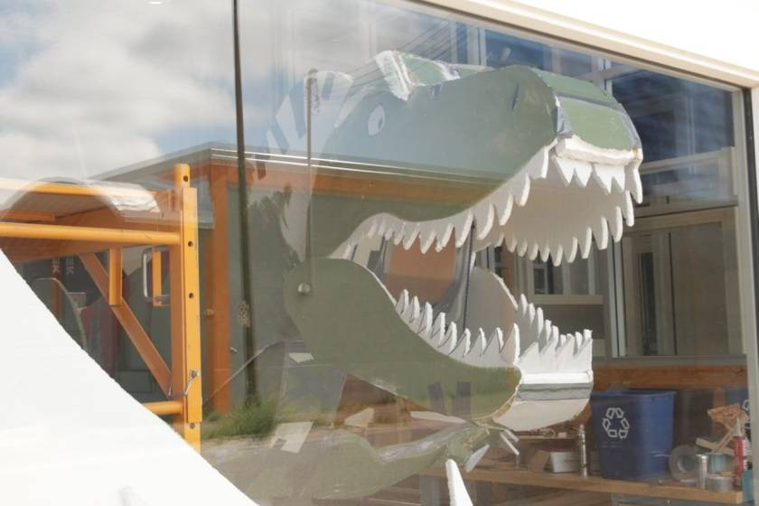 Plain as day – almost – a tyrannosaurus snarls through the windows of the garage at Caztek engineering at 628 Pine Street North at University Avenue.