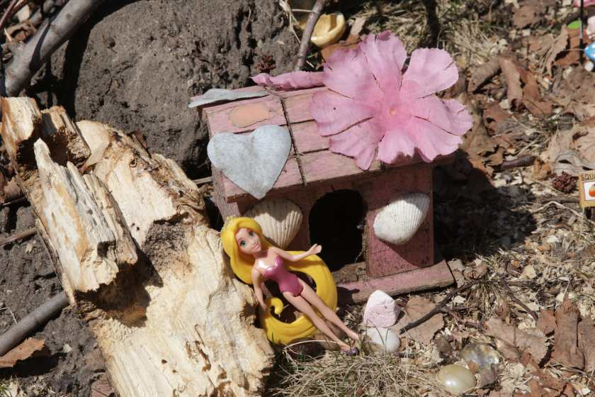 One doll soaks up the sun next to a cabin.