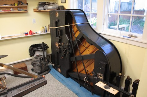 A concert piano doing an impression of an upright in Mark's workshop.