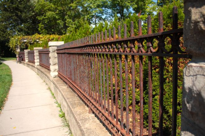 A long-standing wrought iron fence discourages uninvited guests from enjoying the back yard.