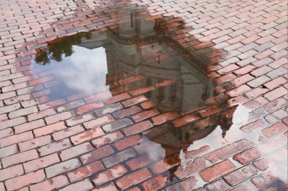 The Saint Paul Cathedral is reflected in a standing pool of water from a recent rain on Maiden Lane.