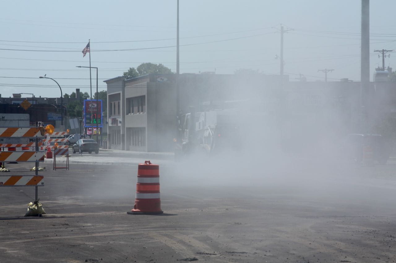 A street sweeper is nearly obscured by the cloud of dust it kicked up.