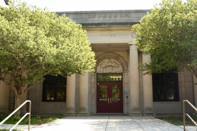 The original main entrance with its prominent frieze above it faces Wheelock Parkway.)