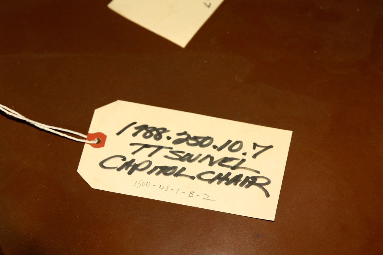 An accession label attached to a chair from the Capitol allows Dan and other collections staff to keep track of artifacts. Every single artifact in the Historical Society collection has a unique accession number.