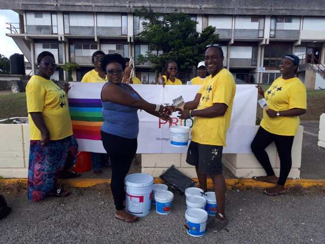 Paint-splattered volunteers from Montego Bay Pride pose with an administrator from Cornwall Regional Hospital. (Photo courtesy of Maurice Tomlinson)
