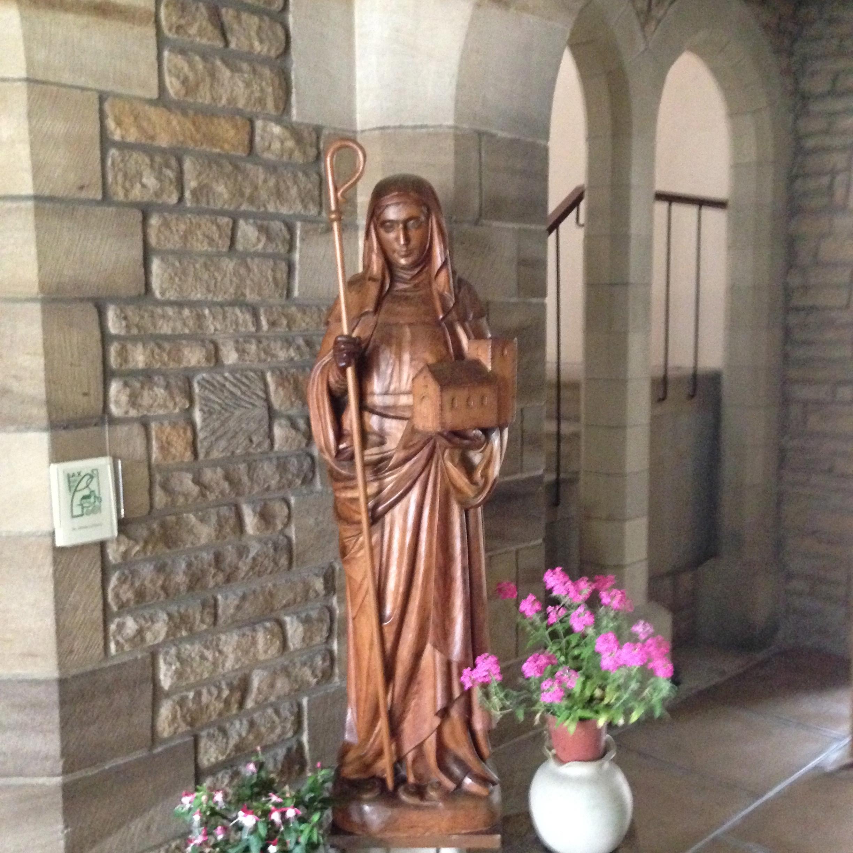 Statue av St. Hilda utenfor det tidligere St. Hilda's Priory Chapel i Sneaton Castle i Whitby. Hun holder en abbedissestav i høyre hånd og en modell av sin klosterkirke i venstre hånd
