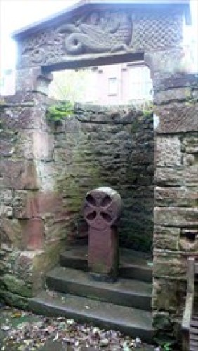 Red sandstone cross under Dragon stone (likely St. Michael fighting off the dragon). Near entry to St. Bee's Priory. Saw this in 2012