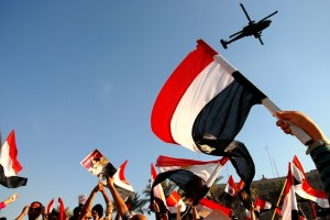 "Pro-Military supporters cheer ""The people and the military are one hand"" in Tahrir Square on July 26, 2013 as military helicopters fly overhead. (SARAH RASHID)"