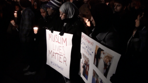 Onlookers hold signs at the Dupont Circle vigil on Thursday, Feb. 12, in Washington, D.C., where they remember the three North Carolina students killed last Tuesday in Chapel Hill. (Photo: SAIS Observer)