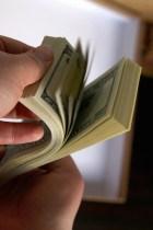 Paquete de dólares en manos de