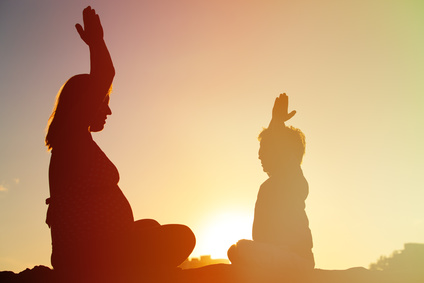 Silhouette of pregnant mother and son doing yoga on beach
