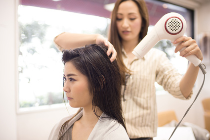 Beautician is dry the hair of women