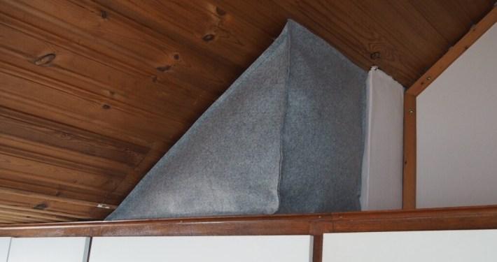 opberger van lichtgrijsvilt, welke precies onder het schuine dak past