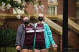 A pair of orientation leaders were stationed outside at each check-in point to take the students' and their family's temperature before entering the dorm buildings.